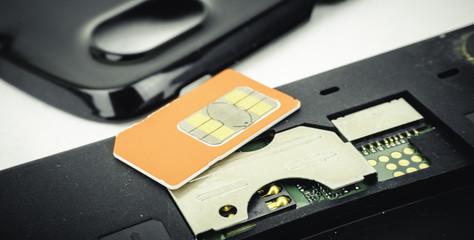 SIM card on black smart phone keypad