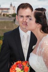 Glückliches Brautpaar posiert vor Kamera mit Brautstrauß