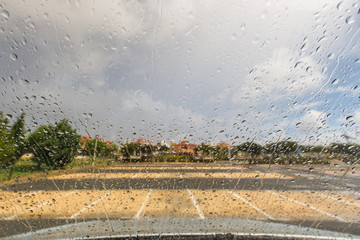 Rain drops on a windscreen in an empty parking lot