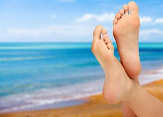 Female feet against blue sea and sky