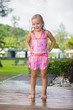 Adorable girl take shower under tree at tropical beach resort
