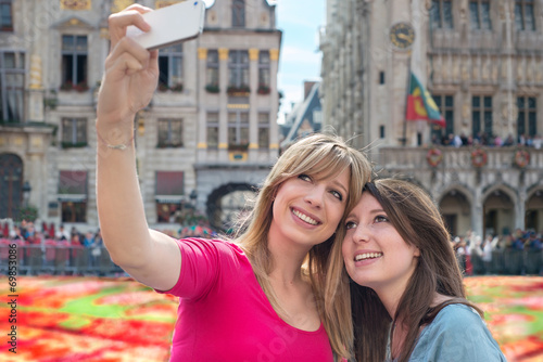 Fototapeta women taking a self portrait with smartphone against flower carp