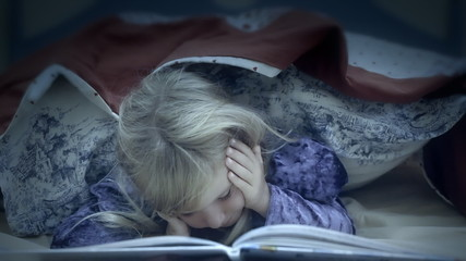 Little girl under bed sheets reading yawning sleeping