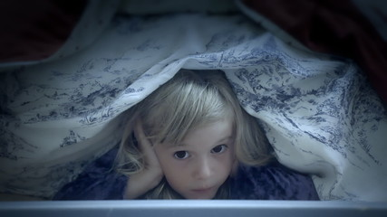 Little girl under bed sheets scared