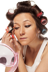 satisfied housewife with curlers applied pencil on the eyes