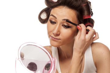 satisfied housewife with curlers applied pencil on eyebrows