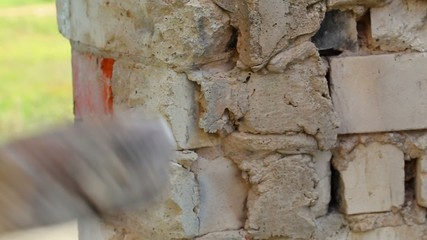 Man with sledge-hammer destroying old wall