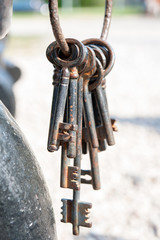 A bunch of old rustic keys. Outdoors.