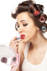 satisfied woman with curlers and bad makeup applied lipstick
