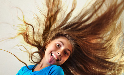 adorable child with longhair sticking her tongue out