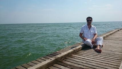 Junger Mann auf Steg am Meer