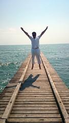 Mann gutgelaunt Sprung auf Steg am Meer