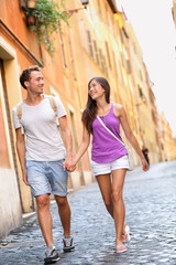 Young casual couple holding hands walking