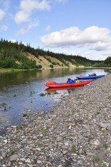 Inflatable kayaks on the shore taiga rivers.