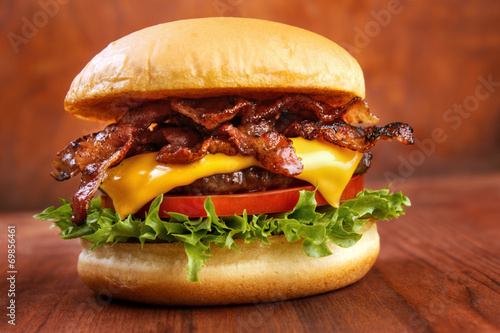 Bacon burger with beef patty on red wooden table poster