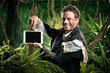 Businessman with tablet in the jungle