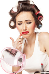 dissatisfied unhappy woman with curlers and with smeared makeup