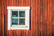 Square white window in old red wooden barn wall