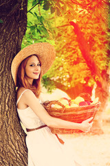 Beautiful redhead girl with fruits in basket at garden.