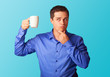 Surprised man in shirt with cup on blue background.
