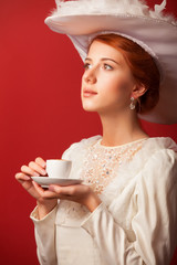 Portrait of redhead edwardian women with cup on red background.