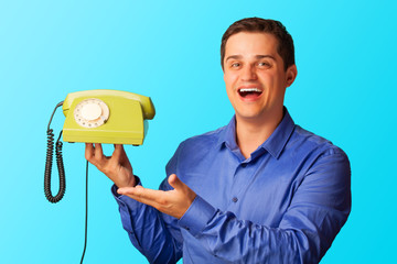 Surprised man in shirt with telephone on blue background.
