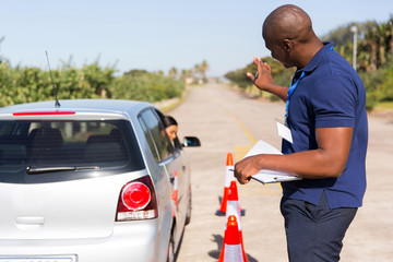 african instructor teaching learner driver to park a car