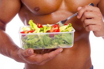Close-up of a muscular man holding a bowl of fresh salad on a wh