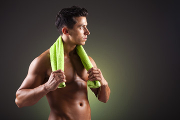 Athletic man holding a green towel on black background