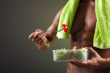 Strong man holding a bowl of fresh salad on black background