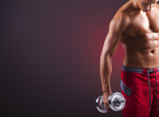 Muscular man doing exercises with dumbbells on black background