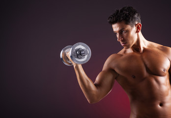 Muscular man lifting dumbbells on black background