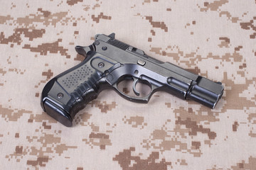 handgun on camouflage uniform