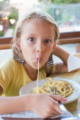 Adorable little girl eating spaghetti in outdoors restaraunt