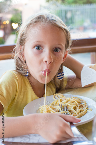 Papiers peints Cuisine Adorable little girl eating spaghetti in outdoors restaraunt