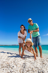 Young beautiful family of three have fun on tropical vacation