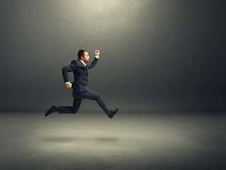 man in suit running fast in the dark room