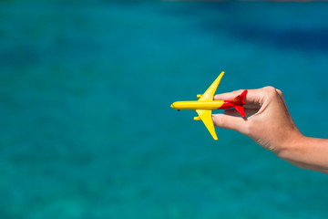 Small homemade plane in female hand on background of the sea
