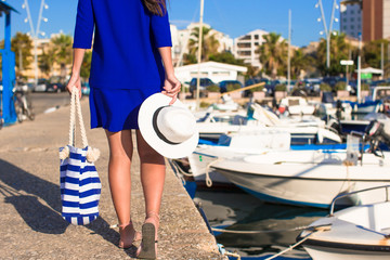 Young beautiful woman walking with hat and bag on dock near the