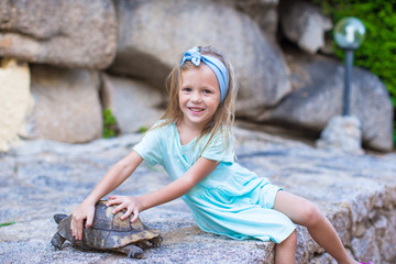 Little adorble happy girl with a turtle outdoors