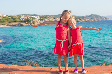 Adorable little girls at tropical beach during summer vacation