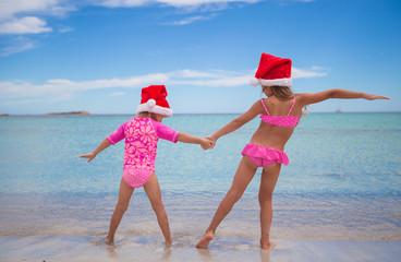 Little cute girls in Santa hats having fun on exotic beach