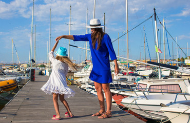 Young mother with little pretty girl in the port enjoying sunny