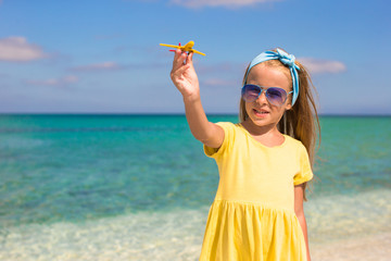 Happy little girl with toy airplane in hands on white sandy