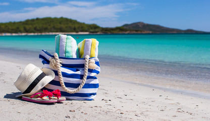 Beach bag, straw hat, flip flops and towel on white tropical