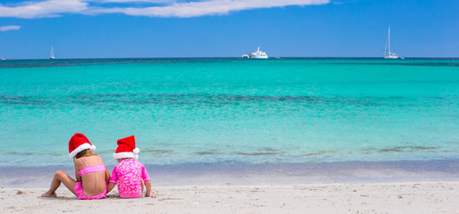 Little adorable girls in Santa hats during their beach tropical