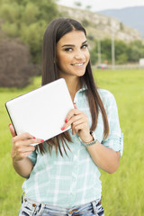 Happy woman holding a tablet in park with a green background