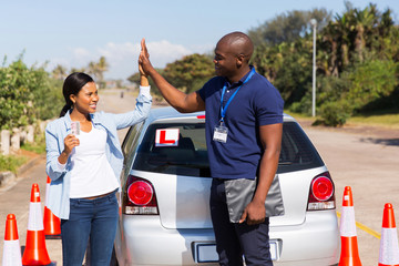 african girl and driving instructor doing high five