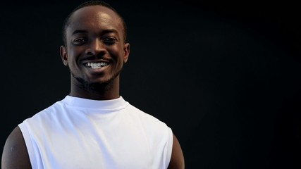 Afro-american sport man on black background smiling