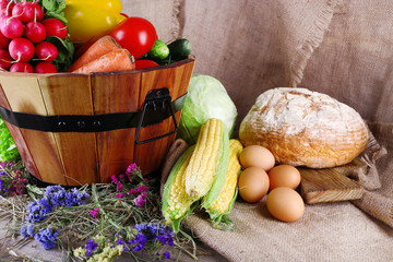 Big round wooden basket with vegetables, milk and bread